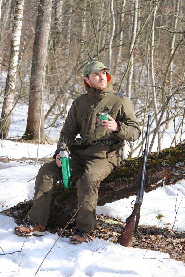 Jägermann trinkt Rest und trinkenden Tee im Wald lizenzfreie stockbilder