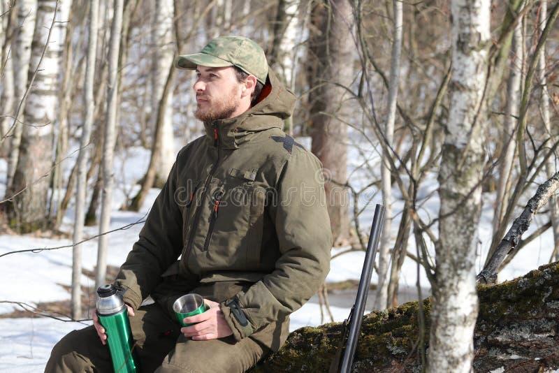 Jägermann trinkt Rest und trinkenden Tee im Wald lizenzfreies stockbild