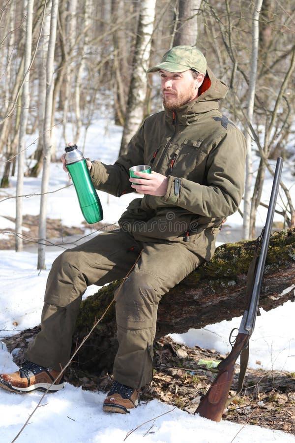 Jägermann trinkt Rest und trinkenden Tee im Wald stockbilder