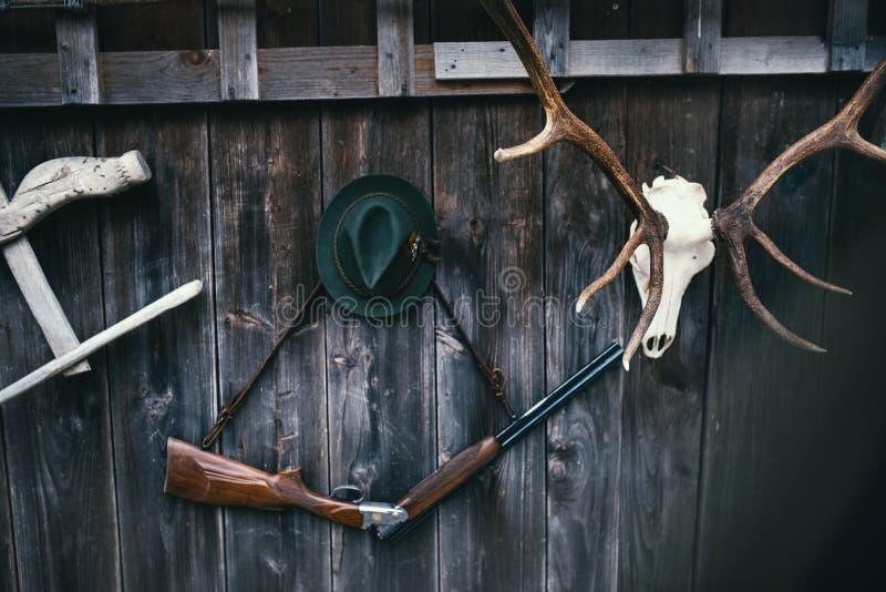 Jägermeisterausrüstung für die Jagd Gewehr-, Rotwild-, Rehtrophäe sculs und andere auf einem hölzernen schwarzen Hintergrund Trop lizenzfreies stockbild