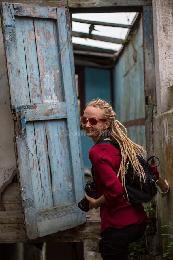 Jägersmädchen erforscht verlassenes Haus mit der Kamera stockfoto
