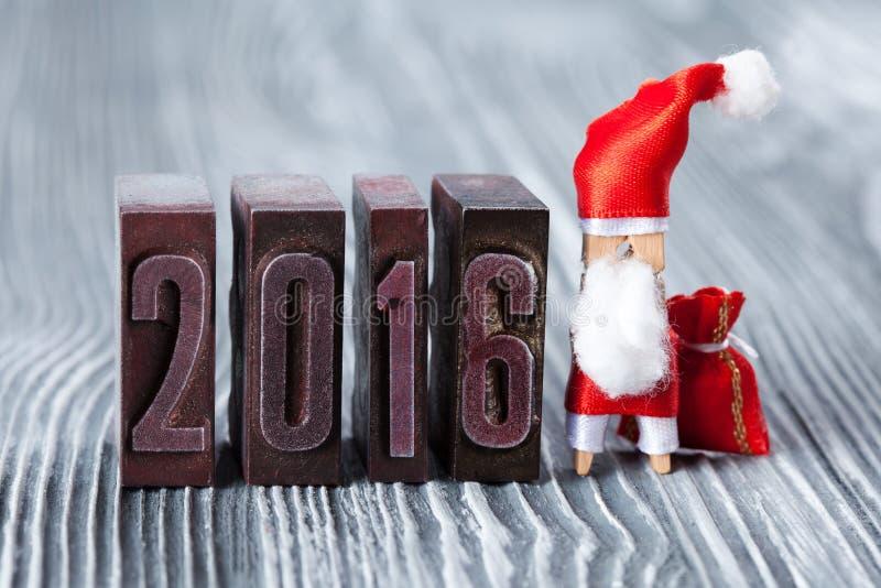 2016-jährig geschrieben mit farbigem Weinlesebriefbeschwerer Weihnachtskonzept - Wäscheklammer Santa Claus mit einer Tasche von G stockbild