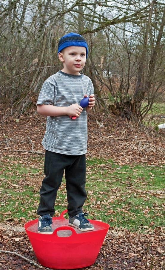 5-jährig-Junge, der auf eisigem rotem Eimer steht lizenzfreie stockfotografie