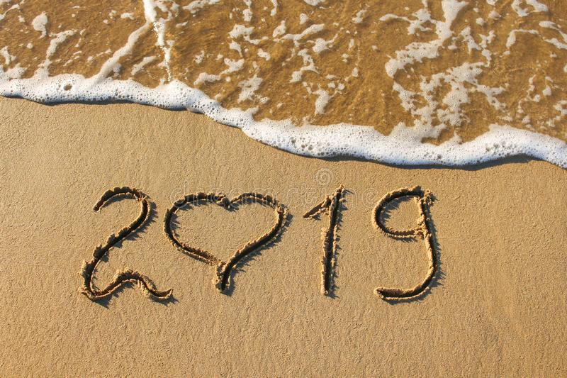 2019-jährig und Herz geschrieben auf Meer des sandigen Strandes stockfoto