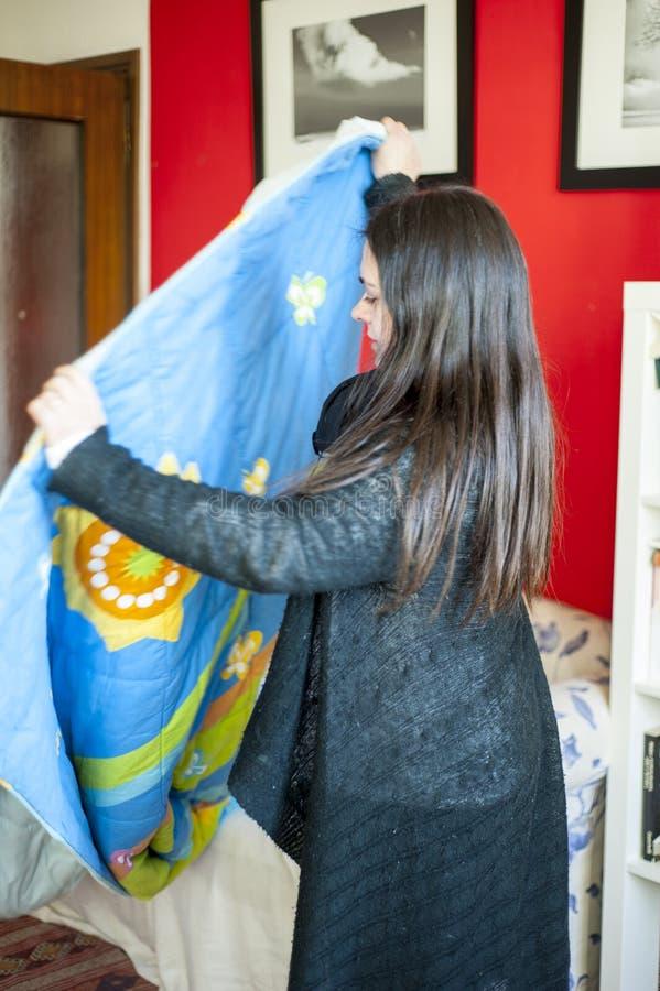 35-jährige Frau in ihrem Haus faltet eine Decke zusammen stockbilder