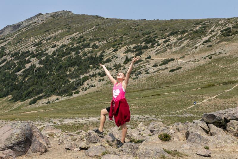Jährige kaukasische Stellung elf mit den Armen und Gesicht erhob zum Himmel entlang einer Spur im Berg Rainier National Park, Was stockbilder