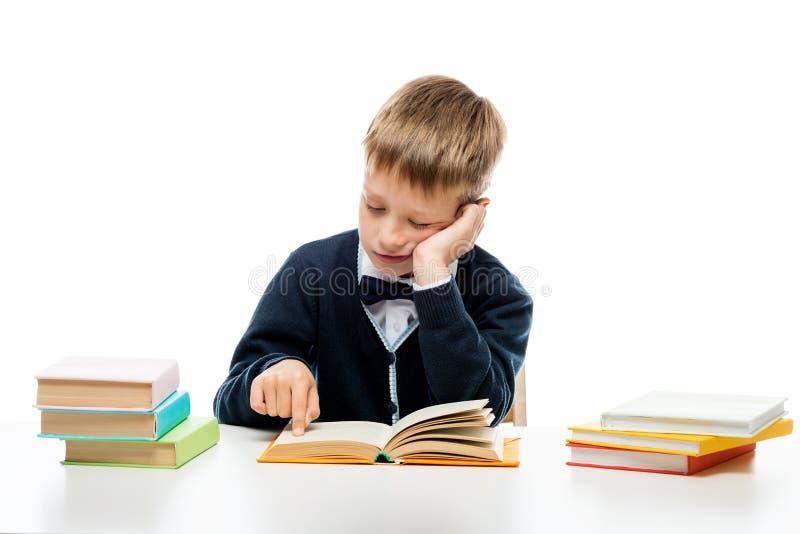 8-jähriger Schüler, der ein Buch an einem Tisch, Porträtisolat liest stockbild