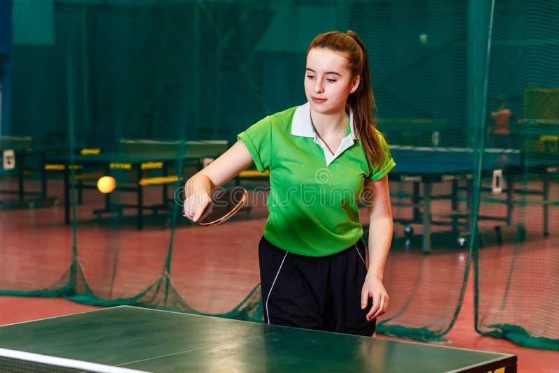 Jähriges jugendlich Mädchen fünfzehn im grünen Sportt-shirt, das Tischtennis spielt stockfoto