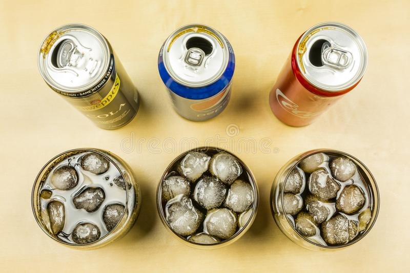 Jämförelse av en coladrink från producenter: Pepsi, coca - cola och Schweppes Cola hälldes in i exponeringsglas med iskuber royaltyfri bild