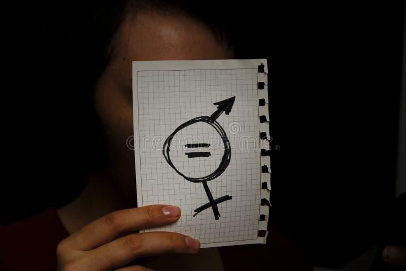 Jämliketecken och ett manligt symbol som dras på ett stycke av papper som visar den sexuella jämställdheten för kvinnor jämställd royaltyfri foto