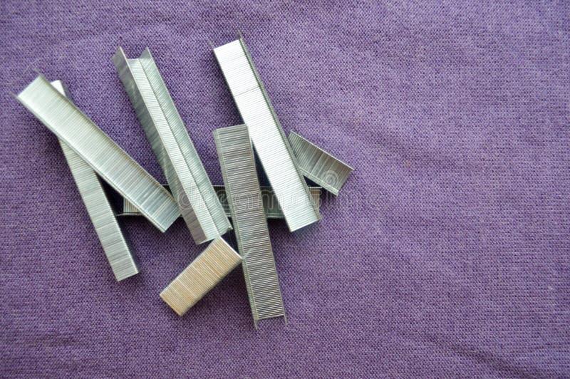 Järn metall, silvriga konstruktionshäftklamrar arkivfoton