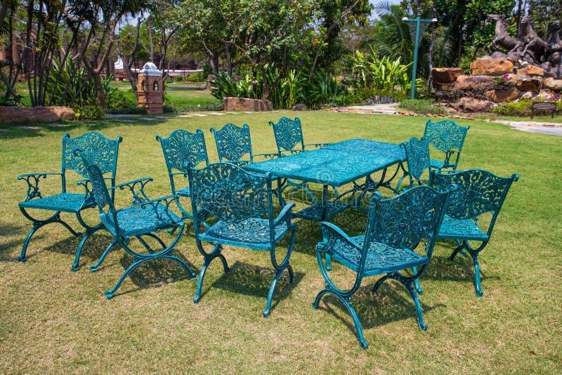 Järngräsplanstolar och tabell som är utomhus- i trädgården fotografering för bildbyråer