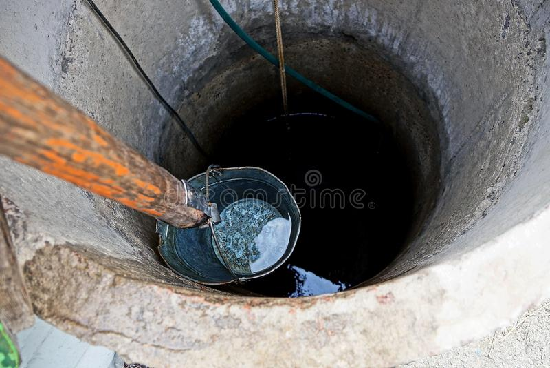Järnhink med vatten på djupet av en rund brunn arkivfoton