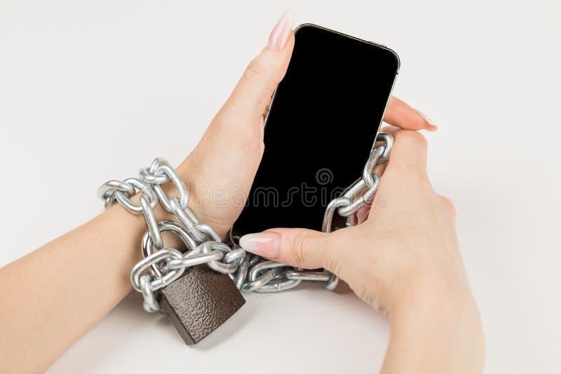 järnkedjan med låset förbinder den kvinnliga handen och smartpen royaltyfria foton