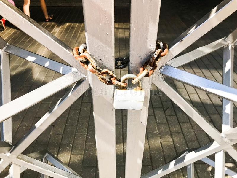 Järnportar, staket för metallstång som frysas på en stark gammal rostig kedja av sammanlänkningar på ett stort lås för spannmålsm royaltyfria foton