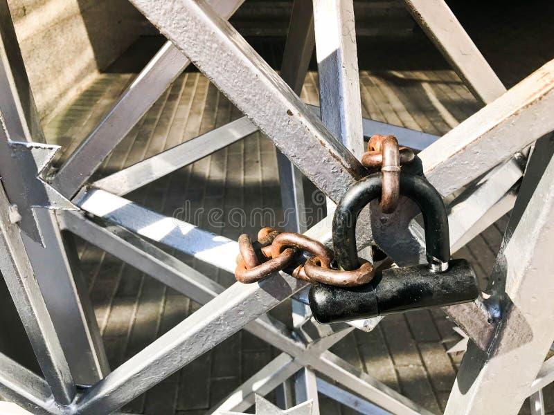 Järnportar, staket för metallstång som frysas på en stark gammal rostig kedja av sammanlänkningar på ett stort lås för spannmålsm arkivfoto