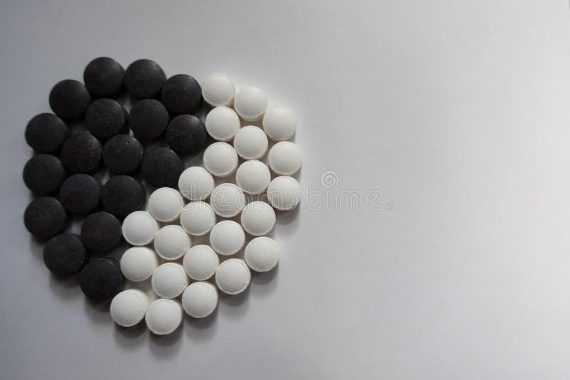 Järnsvart och vita piller för vitamin K i form av yin och det yang symbolet arkivbild