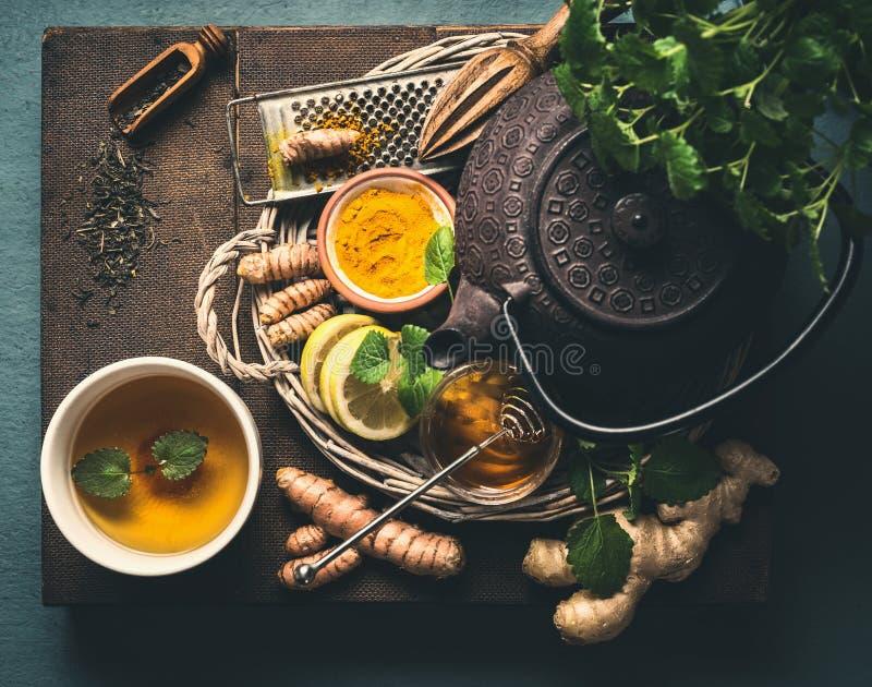 Järntekanna med nya växt- ingredienser för ljust rödbrun te för sund gurkmeja med citronen och koppen av guld- gurkmejate på mörk fotografering för bildbyråer