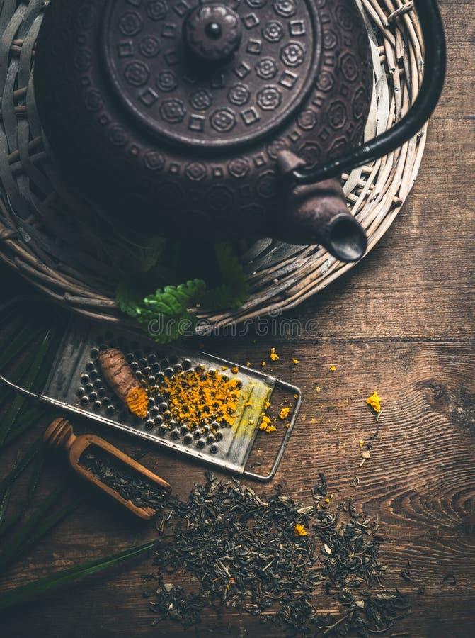 Järntekannan med ny gurkmeja rotar och rivjärnet på lantlig träbakgrund, bästa sikt Naturlig immun ökande bot royaltyfri bild