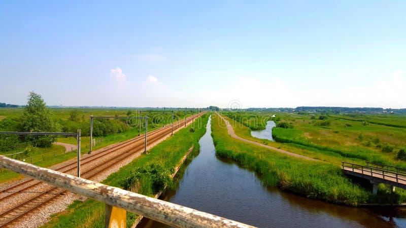 Järnväg bredvid en flod och grönområden arkivbild