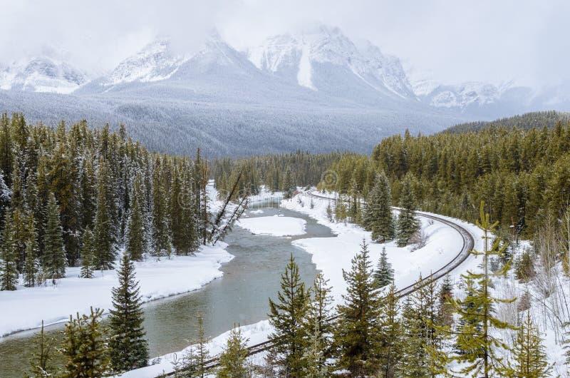 Järnväg hals längs sida en flod i ett berglandskap i vinter arkivfoto