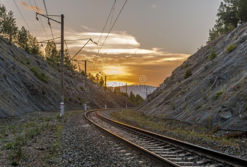 Järnväg i bergen på solnedgången royaltyfri bild