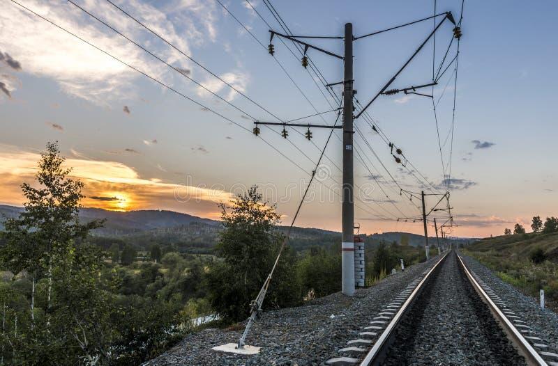 Järnväg i bergen på solnedgången arkivbilder