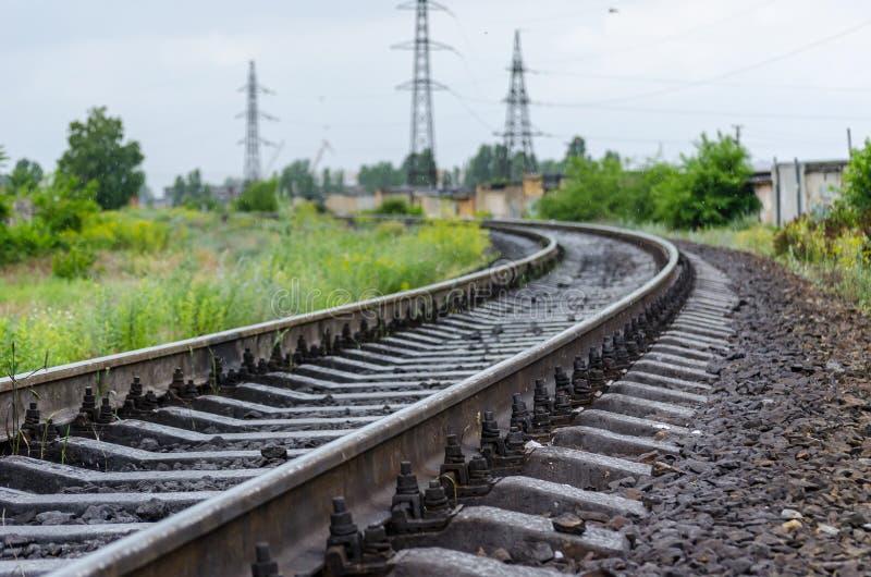 Järnväg i regnet som försöker att fly från de envisa dropparna runt om krökningen arkivbilder