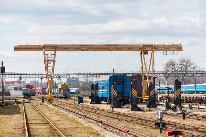 Järnväg lastningsbryggakran på punkt av den avkopplade reparationen av vagnar och drev för lokomotiv järnväg på bussgaragestation arkivfoton