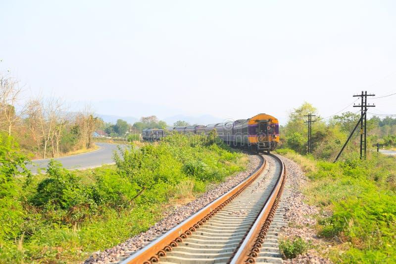 Järnväg linje bortgång till och med de gröna växterna Resaväg med drevet arkivbild