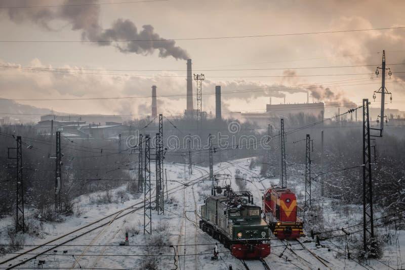 Järnväg och en rökväxt i bakgrunden arkivfoton