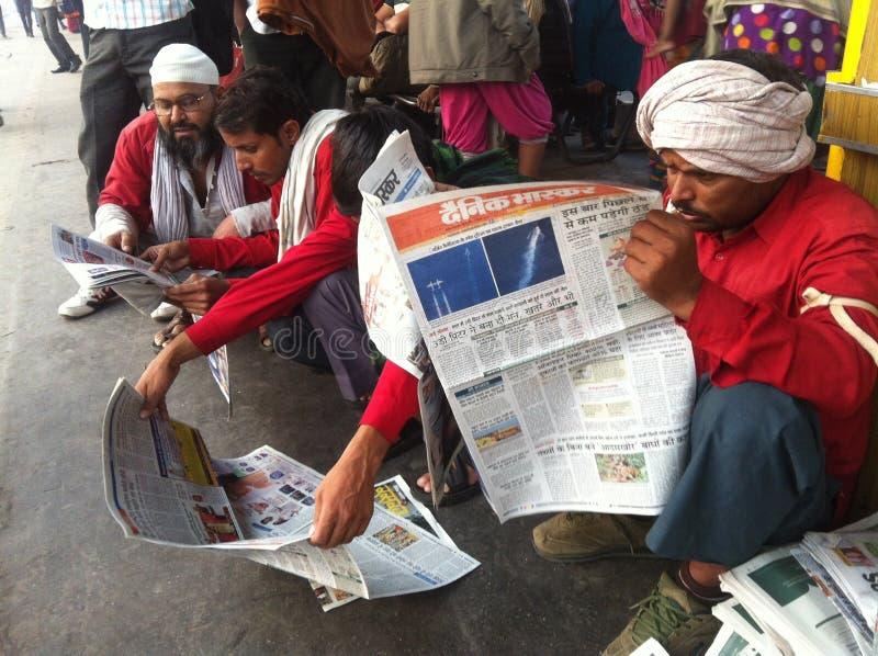 Järnväg portvakter som ner sitter och tidigt på morgonen läser tidningarna royaltyfri fotografi