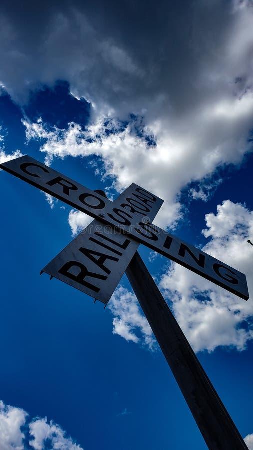 Järnvägkorsning tecken med moln arkivfoto