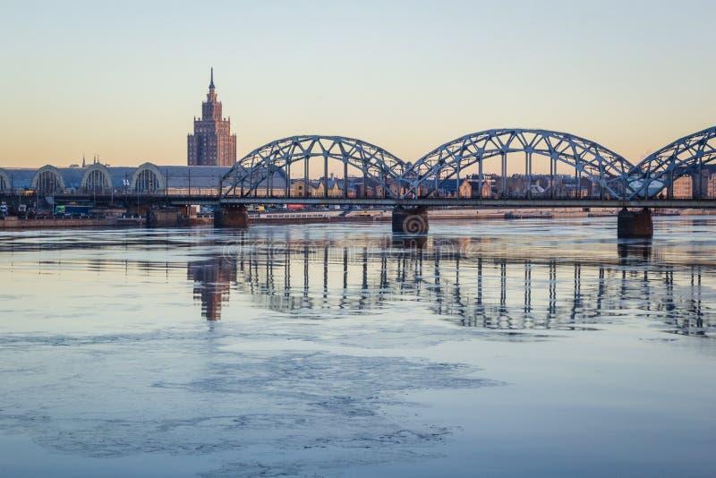 Järnvägsbro över den djupfrysta floden i den snöig vintern Riga under solen fotografering för bildbyråer