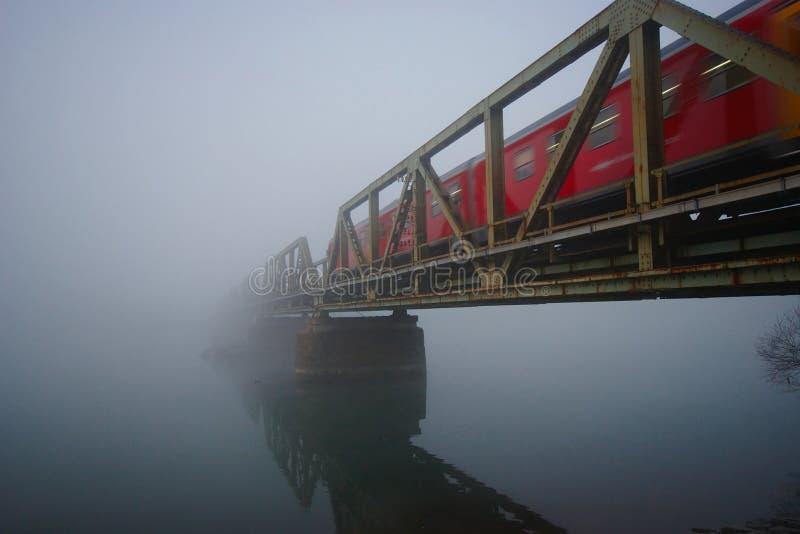 Järnvägsbro med det röda drevet i dimman arkivfoton