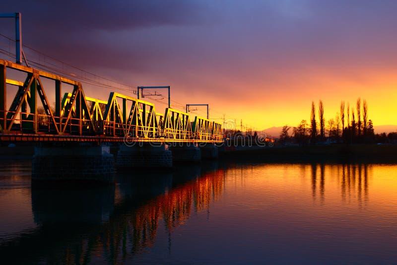 Järnvägsbro på solnedgången arkivfoton