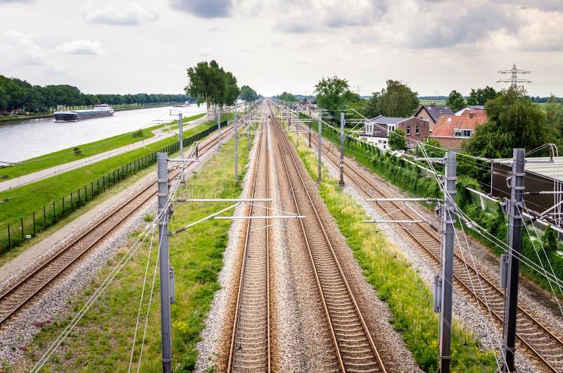 Järnvägspår i bygden av Nederländerna på en molnig dag royaltyfri fotografi
