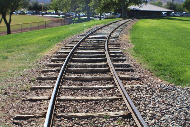 Järnvägspår som buktar in i, parkerar äldre red ut band som flyttar sig in i avstånd royaltyfri bild