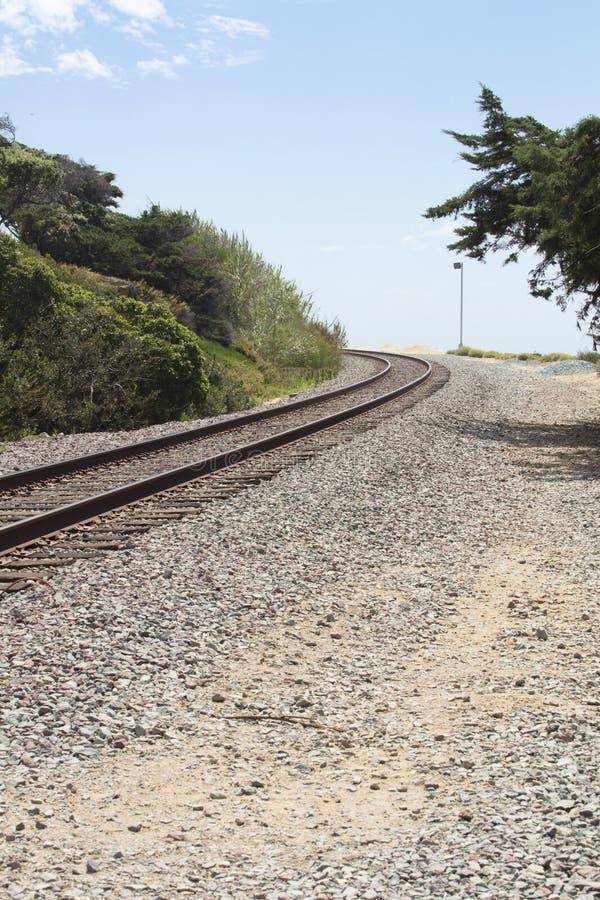 Järnvägspår som buktar runt om en krökning på en grusbana arkivbild