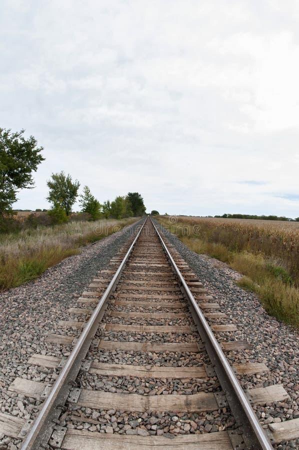 Järnvägspår till och med jordbruksmark arkivbilder