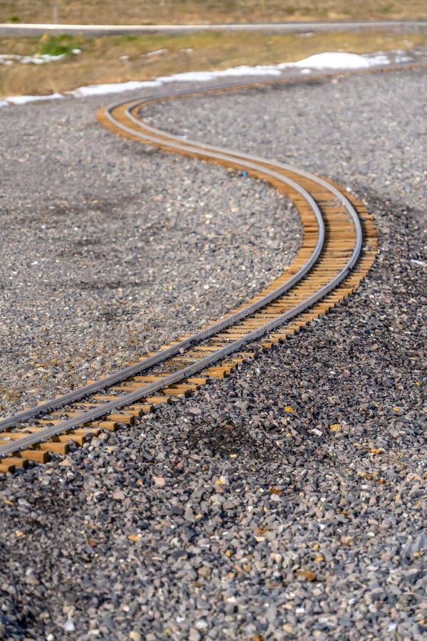 Järnvägsspår som buktar till och med en stenig jordning royaltyfri bild