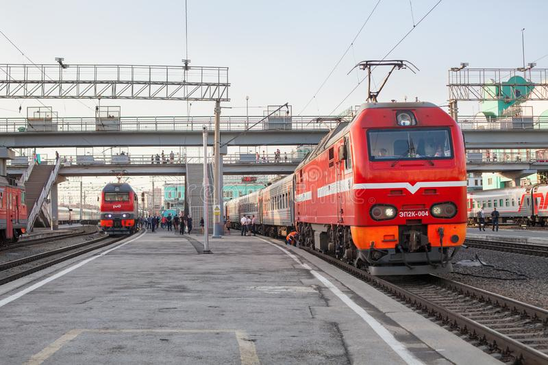 Järnvägsstation i städer, järnvägsvagnar för persontrafik på plattformar nära varandra, rött lok på spår, järnvägstransport arkivfoto