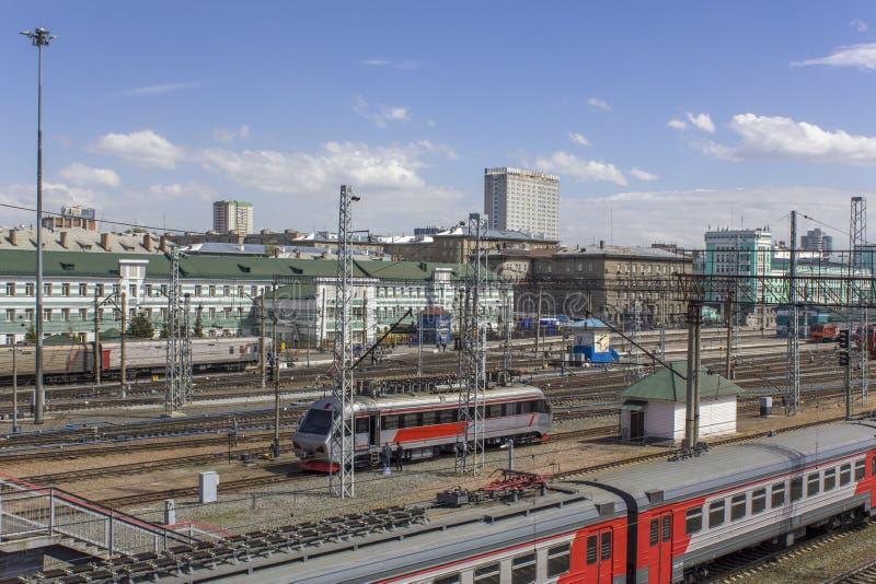 Järnvägsstation med många railtracks och moderna drev och bilar på bakgrunden av staden, flyg- sikt arkivfoton