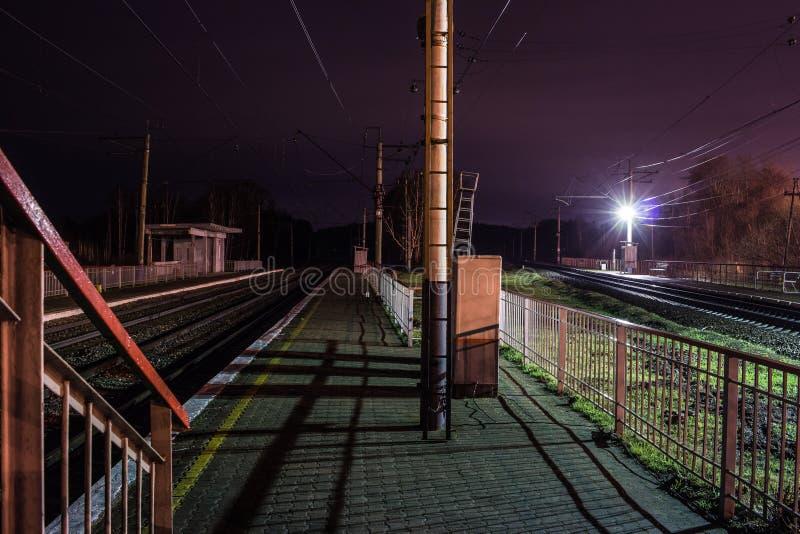 Järnvägsstation på natten med ett övergående drev arkivfoton