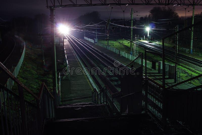 Järnvägsstation på natten med ett övergående drev arkivbild