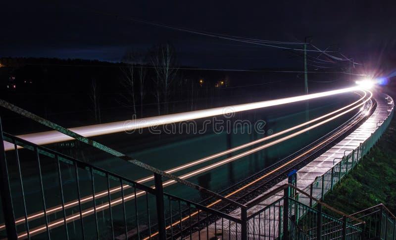 Järnvägsstation på natten med ett övergående drev royaltyfri fotografi