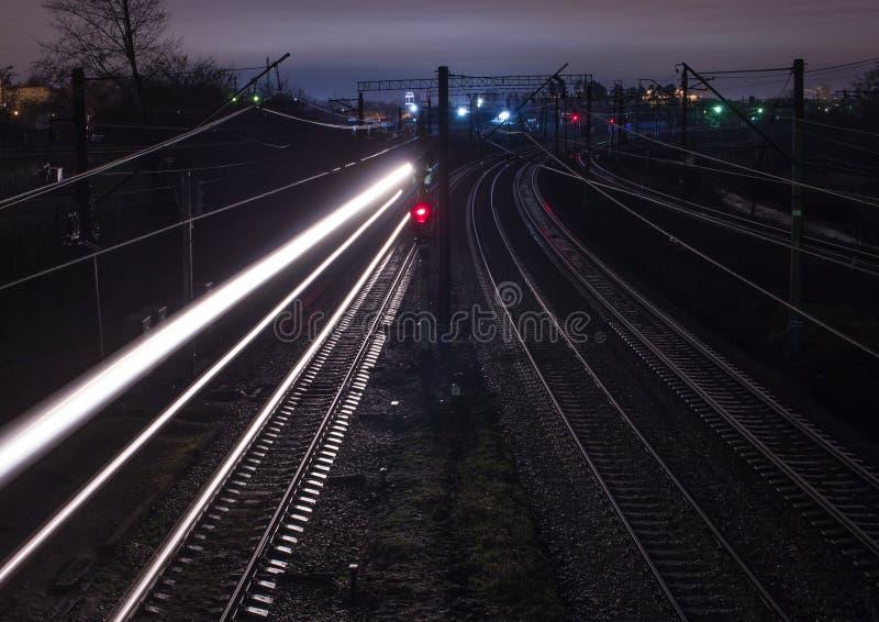 Järnvägsstation på natten med ett övergående drev royaltyfria foton