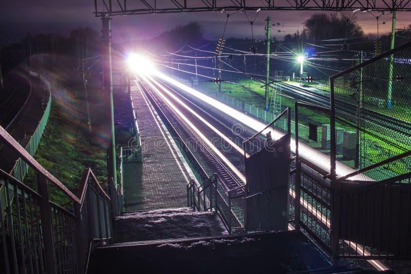 Järnvägsstation på natten med ett övergående drev royaltyfri foto
