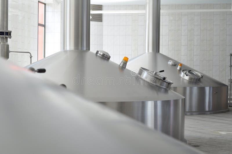 Jäsning i ett bryggeri - behållare med öl för att brygga arkivfoto