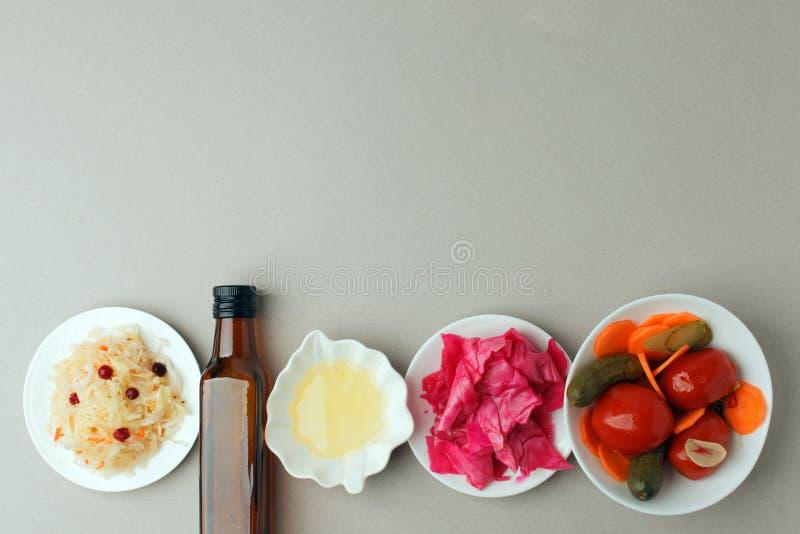 Jäste grönsaker på plattan på grå bakgrund: surkål inlagd kål med rödbeta, inlagda gurkor, morötter och royaltyfria foton
